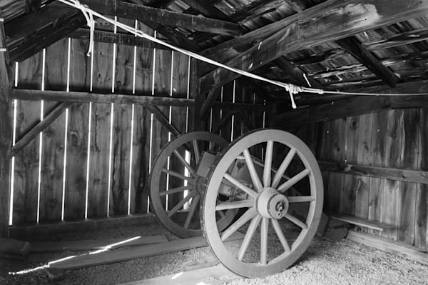 Black & white photograph of old cannon wagons in an abandoned barn in historic Fort George, Ontario, for sale as fine art by Sage & Balm