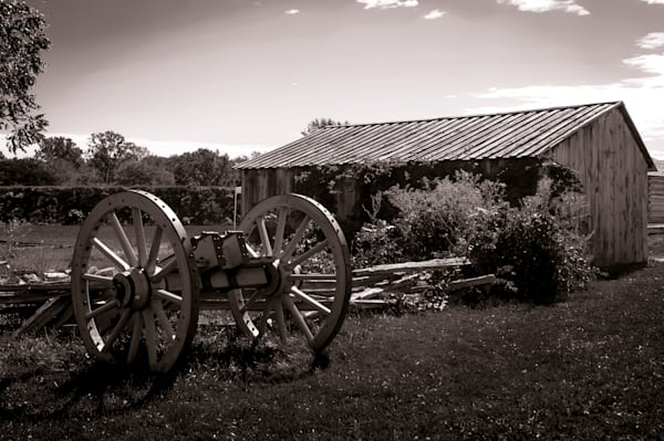 Sepia photograph of an antique cannon wagon and barn from historic Fort George, Niagara-on-the-Lake, for sale as fine art by Sage & Balm