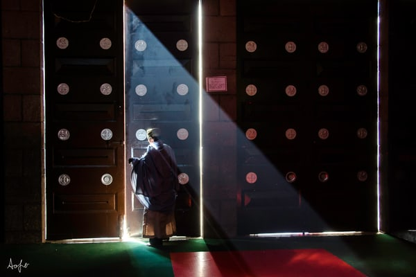 Fine art photograph of priest closing church door with light filtering through