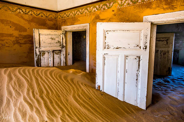 Surreal photograph art of old house filled with desert sand and morning light