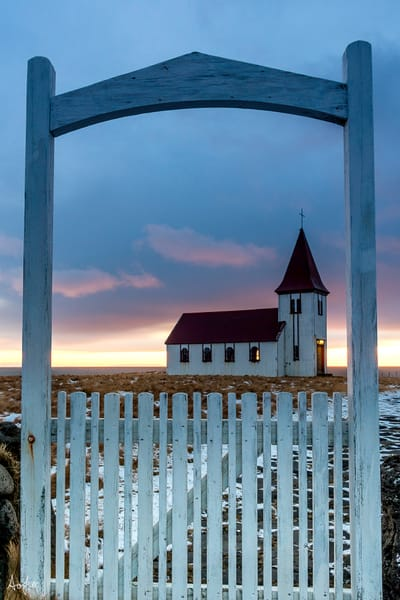 Fine art photograph of Church framed by white gate posts at sunrise