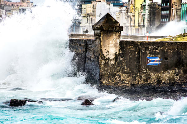 A man stands on the Malecon with waves crashing around him in a powerful  art photograph