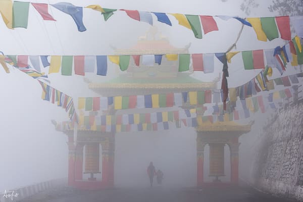 Fine art photograph of mother and child walking through fog under monastery gate