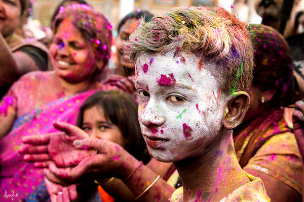 Portrait of boy with white powder on face, during Holi festival in a fine art photograph