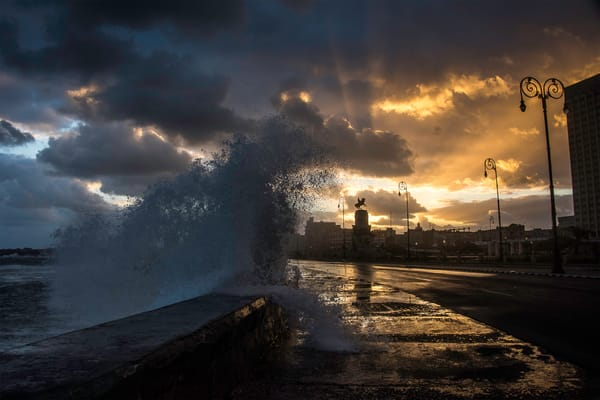 Wave crashing over Malecon at sunrise, with rays coming from clouds, in a fine art photograph