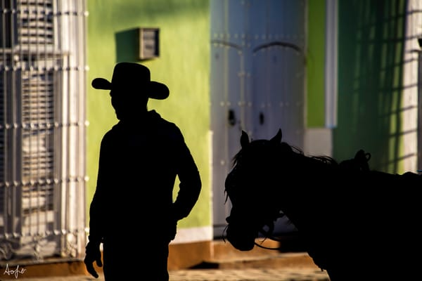 Silhouette of cowboy leading his horse with colorful houses behind in an art photograph