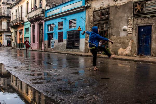 Art photograph of barefoot boy playing soccer in wet havana street