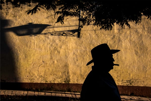 Fine art photograph of a silhouette of man in cowboy hat with cigar in mouth by mustard wall