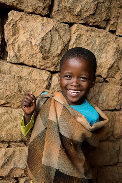 art photograph of smiling Lesotho boy with traditional blanket by stone wall