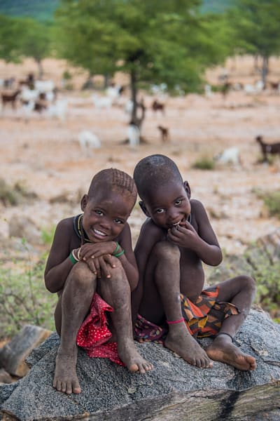 Two young Himba girls smiling, with goats behind them, in a photograph art print