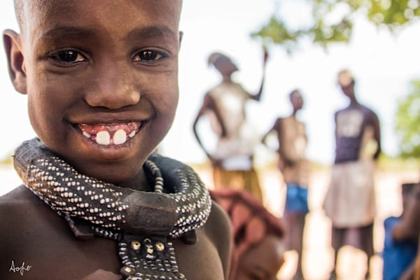 Himba girl with big smile and big necklace, with men in background, fine art photograph print