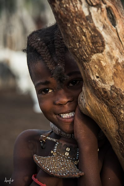 Portrait of Himba girl standing shyly by tree, photograph print art