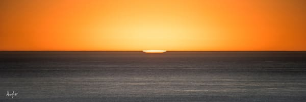 Fine art photograph, panoramic, surreal sunset with a hint of sun on horizon