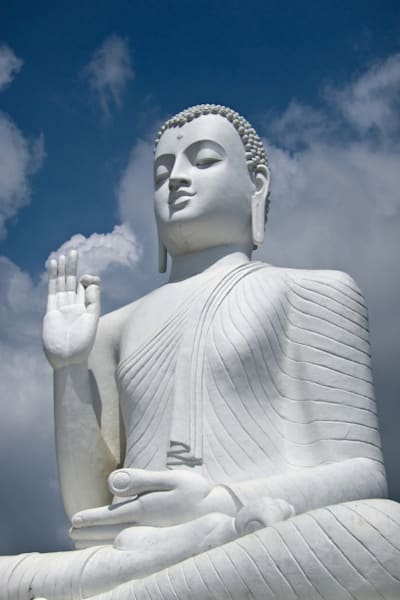 Large white buddha statue in sitting pose, in fine art photograph