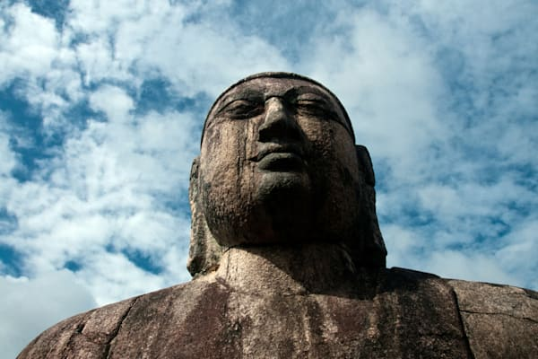 Weathered Buddha statue with blue sky and white clouds above, in art photograph print