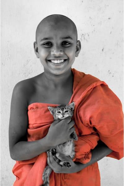 Fine art photograph of novice monk in orange robe holding kitten