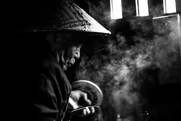 Japanese man in conical hat making tea, in a fine art photograph