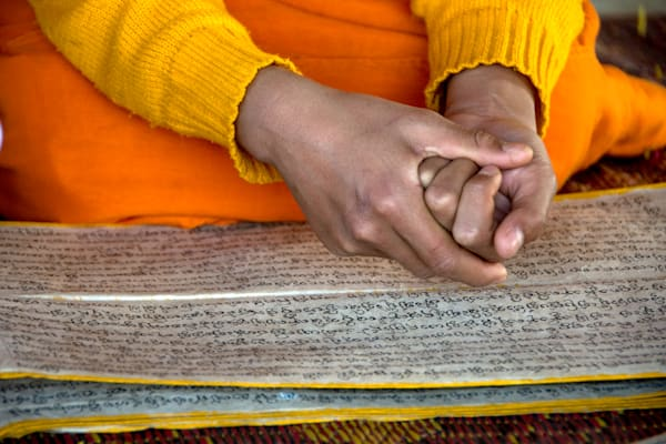Monk's hands over Buddhist scripture in a fine art photograph print