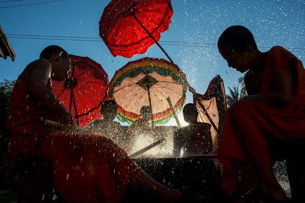 Monks beating a drum under red umbrellas