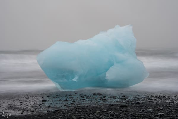 large piece of blue glacier ice on black sand beach, fine art photograph