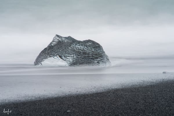 Surreal fine art photograph of large piece of glacier ice on beach
