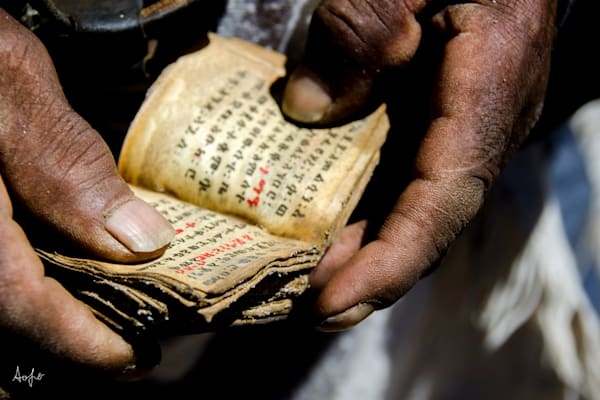 Fine art photograph of man holding a small leather Coptic bible