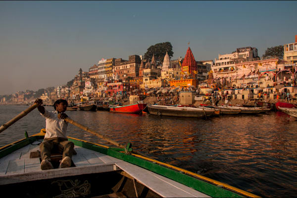 Boy rowing in morning light in Varanasi, in a fine art photograph print