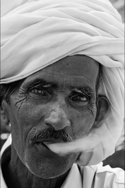 Indian man with white turban blowing smoke, in photograph art print
