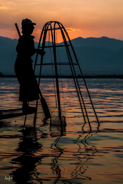 Foot rower in silhouette lifting fish trap at sunrise, in fine art photograph