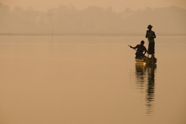 Two fishermen in silhouette with gold morning light, in a fine art photograph print