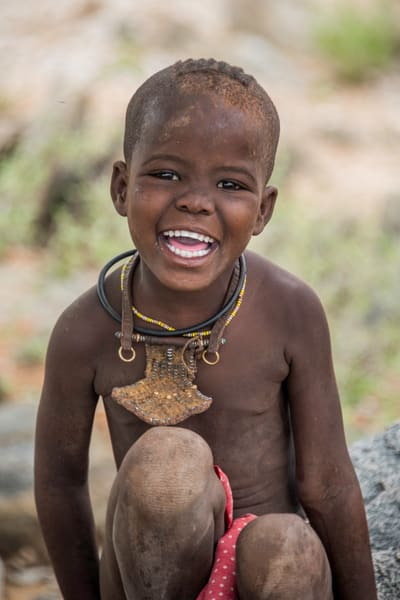 Smiling Himba girl with traditional jewelry