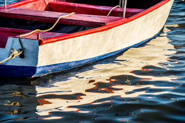 Red, white and blue row boat reflecting in water ripples