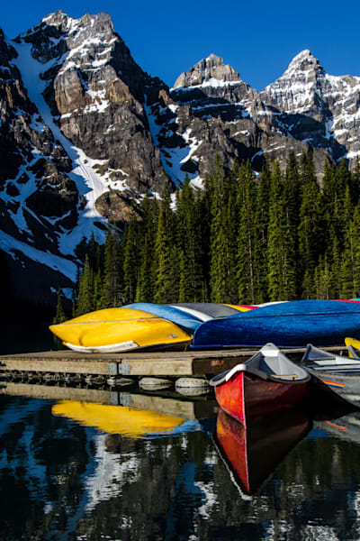 Colorful canoes on Moraine Lake with snow capped peaks.