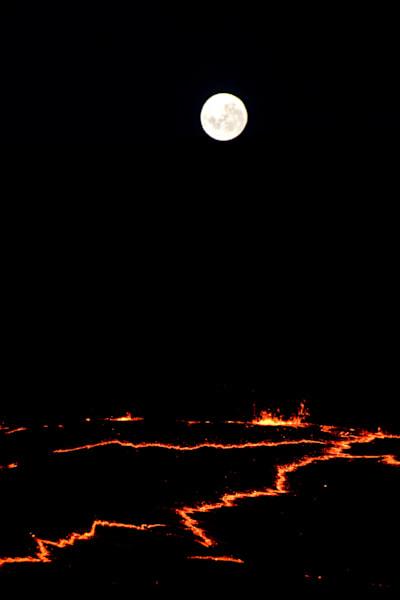 Full moon rising over volcano rim.