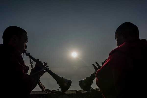 Tibetan monks playing the flute at sunrise