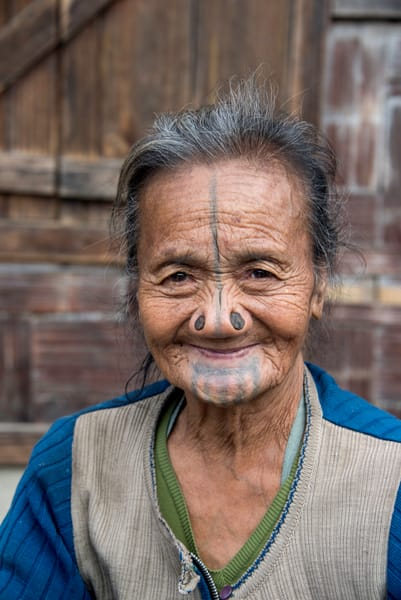 A smiling older Apatani woman with nose plugs and facial tattoos