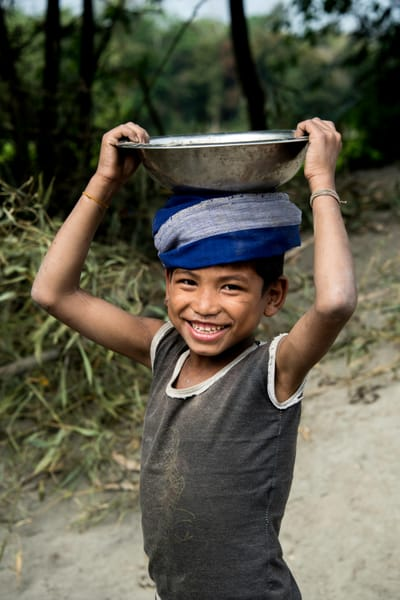 Smiling boy with metal bowl, and blue scarf on head