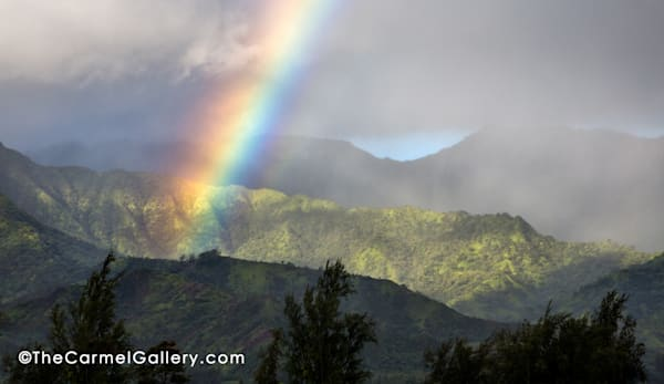 Early morning rain shower and rainbow over Hanalei Bay on Kauai