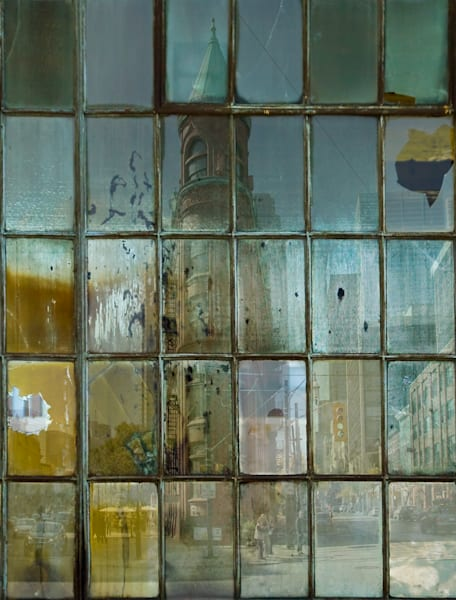 A Photograph of the iconic Toronto Flat Iron Building as seen through stained and rusted industrial window panes for sale by Michael Toole.