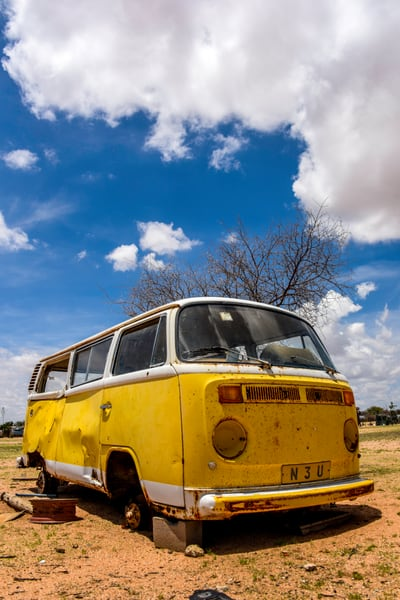 Abandoned yellow Volkswagen bus with blue sky and white cloud, photograph art