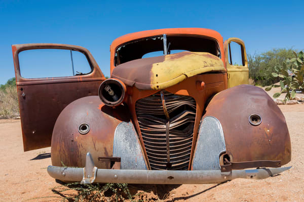 Front view of old Hudson car in the desert in photograph art