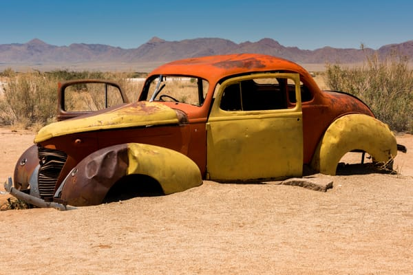 A yellow, orange and brown shell of a car in the desert, in art photograph