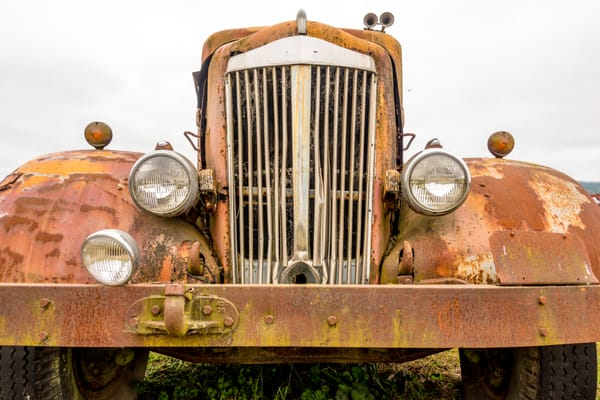 Wide angle of rusty antique car's classic front grille in art photograph