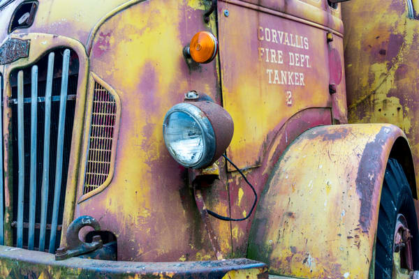 An old fire truck in yellow and pink with nice front grille in art photograph
