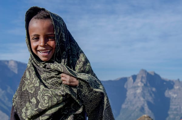 Art photograph portrait of smiling Ethiopian boy, wrapped in blanket