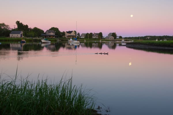 Cape Cod, MA, setting moon, morning light on boats and homes along Snug Harbor