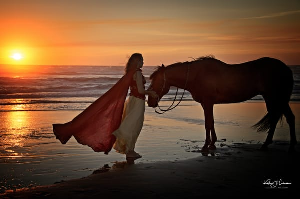 Caped woman on beach with Horse at sunset