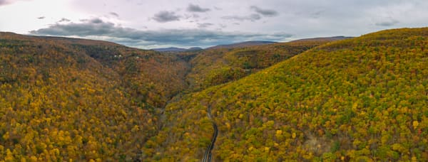 Kaaterskill Falls Aerial Panoramic photograph from a drone of the fall trees and mountains in the background by Steven Archdeacon.