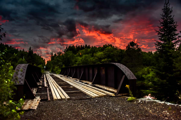 An old iron bridge with a fiery sunset sky, and dark clouds, fine art photograph