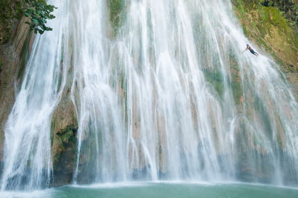 A young man diving off El Limon, the waterfall at Samana, Dominican Republic